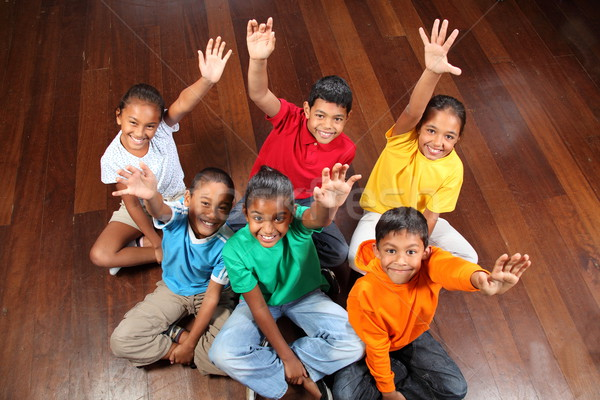 Stock photo: Six young school children sitting on classroom floor arms raised