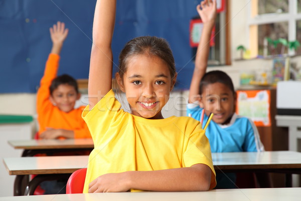 Three primary school children signal they know with raised hands Stock photo © darrinhenry