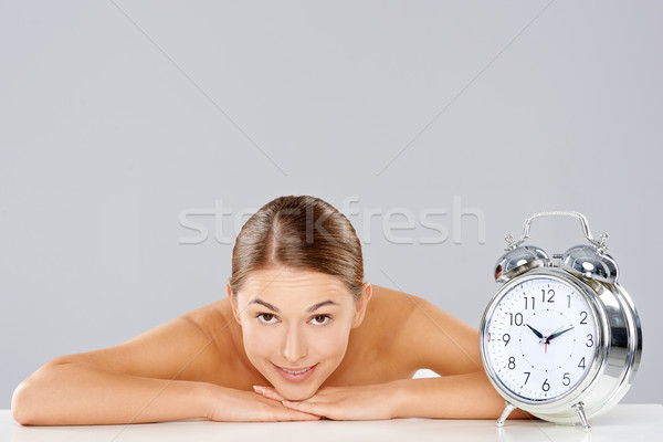 Smiling relaxed woman with an alarm clock Stock photo © dash