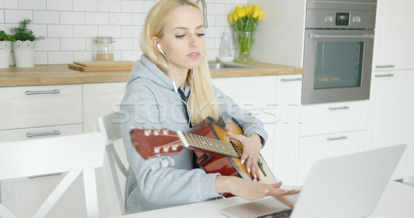 Girl practicing guitar and using laptop  Stock photo © dash