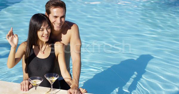 Loving couple smooching at swimming pool Stock photo © dash