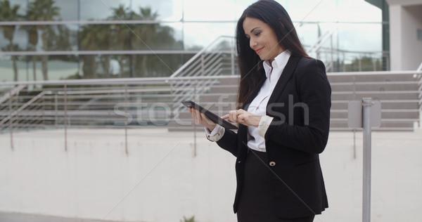 Stylish businesswoman using her tablet Stock photo © dash