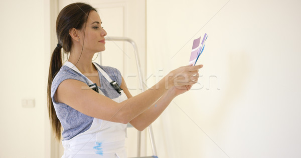 Young decorator deciding on a color of paint Stock photo © dash