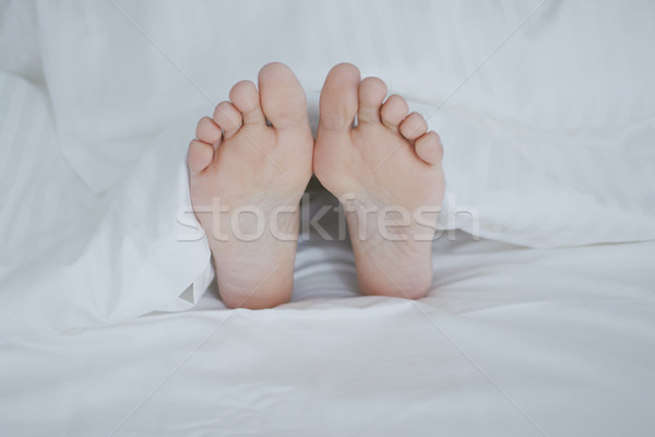 Crop female feet under blanket Stock photo © dash