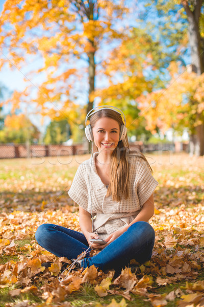 Smiling woman listening to music in a fall park Stock photo © dash