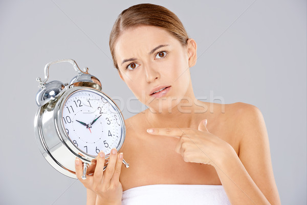 Bored woman with an alarm clock in her hand Stock photo © dash