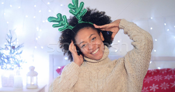 Playful young woman wearing green reindeer antlers Stock photo © dash