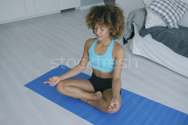 Concentrated woman practicing yoga on mat Stock photo © dash