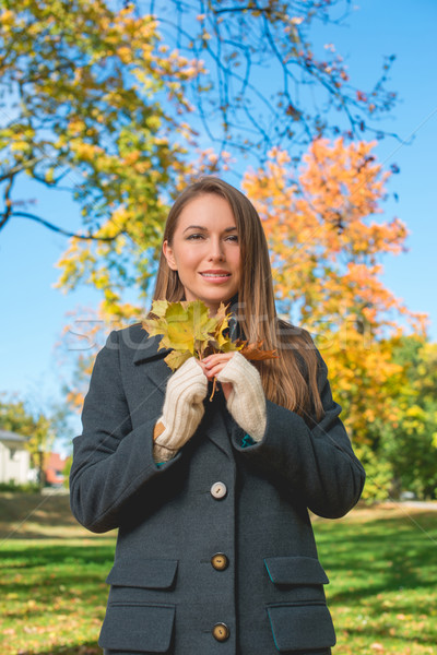 Pretty Lady in Autumn Fashion Holding Dry Leaves Stock photo © dash