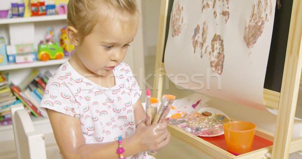 Cute little girl choosing a paint brush Stock photo © dash