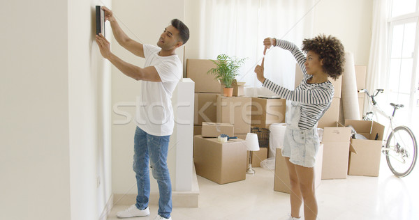 Young couple hanging pictures in their new home Stock photo © dash