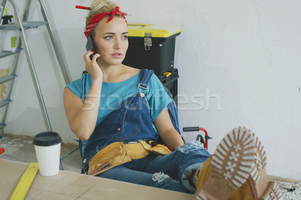 Worried female at workbench talking on smartphone  Stock photo © dash