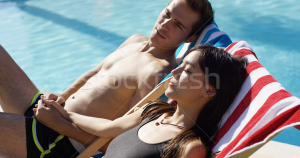 Young couple relaxing poolside in deck chairs Stock photo © dash