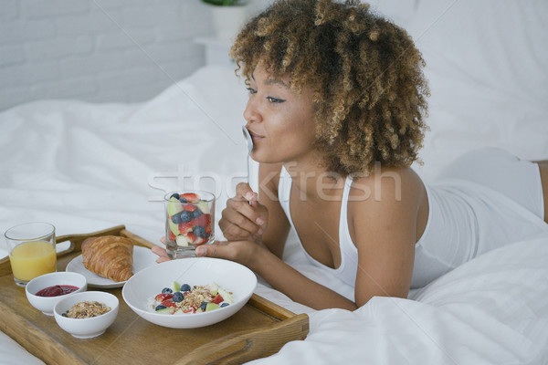 Dreaming woman having sweet meal in bed Stock photo © dash