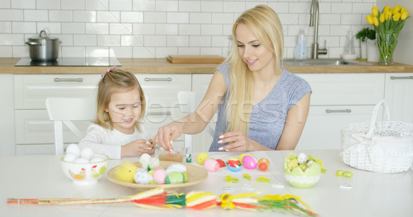 Charming mother and daughter coloring eggs Stock photo © dash
