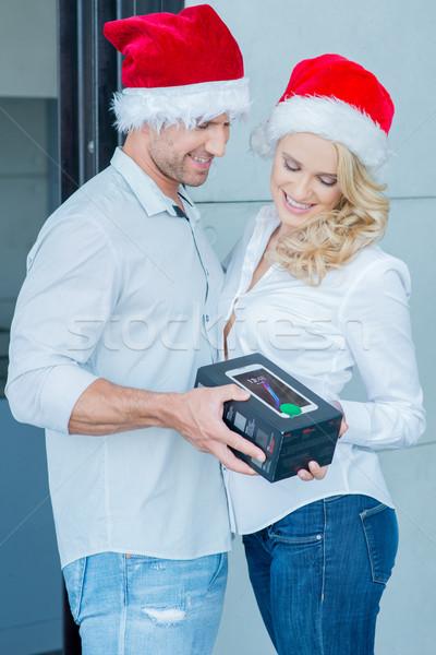 Couple Wearing Santa Hats Exchanging Gift Stock photo © dash