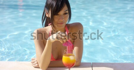 Pretty young woman checking her mobile poolside Stock photo © dash