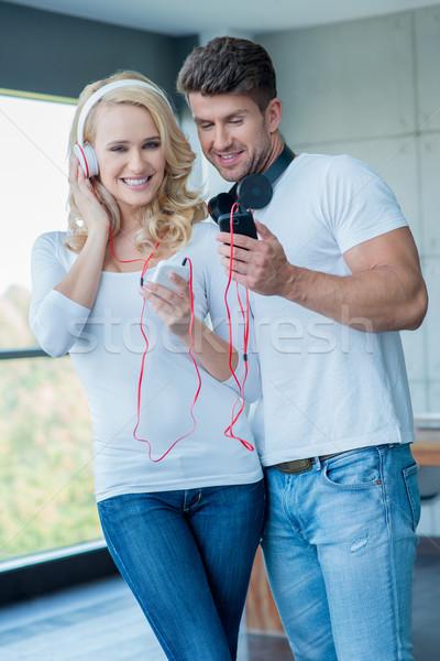 Atraente casal ouvir música fones de ouvido em pé braço Foto stock © dash