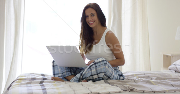 Smiling woman using laptop in bed Stock photo © dash