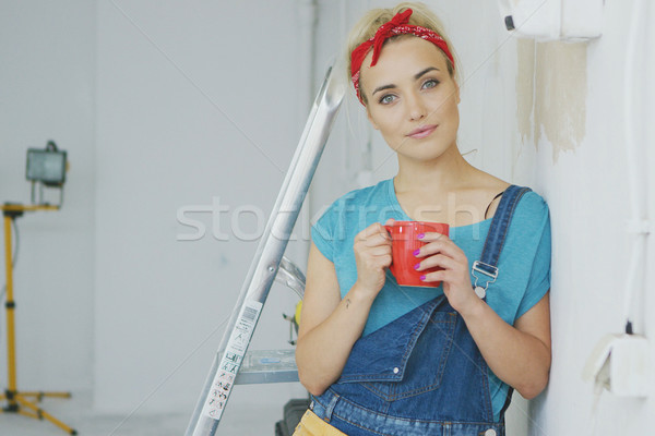 Smiling female in overalls leaning on wall  Stock photo © dash