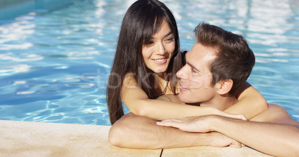 Handsome smiling couple cuddles in swimming pool Stock photo © dash