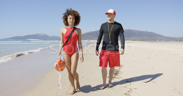 Female and male lifeguards walking along beach Stock photo © dash