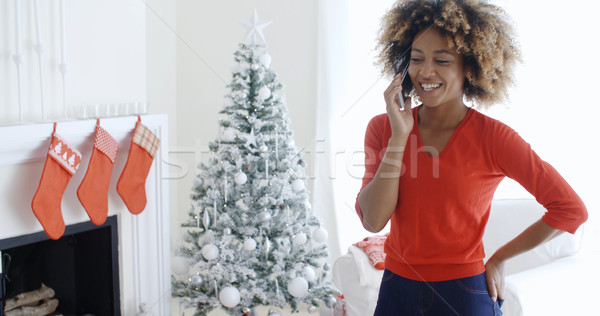 Happy young woman chatting on her mobile at Xmas Stock photo © dash