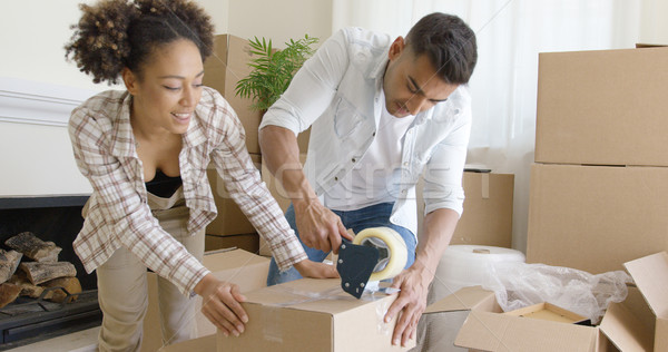 Couple taping boxes as they pack up their home Stock photo © dash