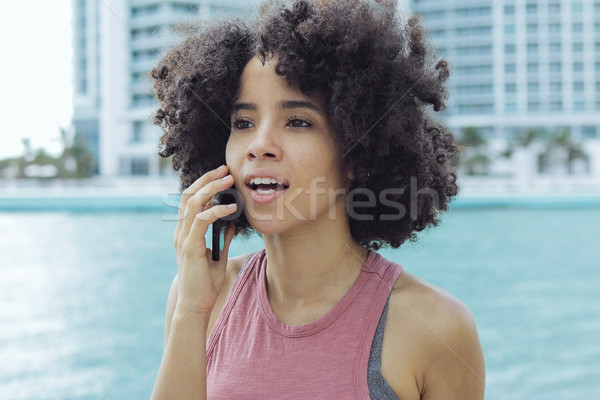 Black girl having phone call on seafront Stock photo © dash