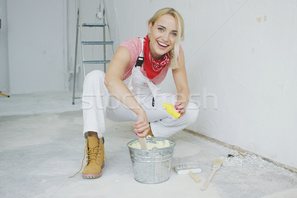 Smiling female mixing yellow wall paint  Stock photo © dash
