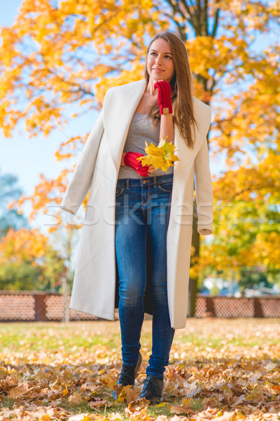 Pretty Woman in Big White Coat Holding Leaves Stock photo © dash