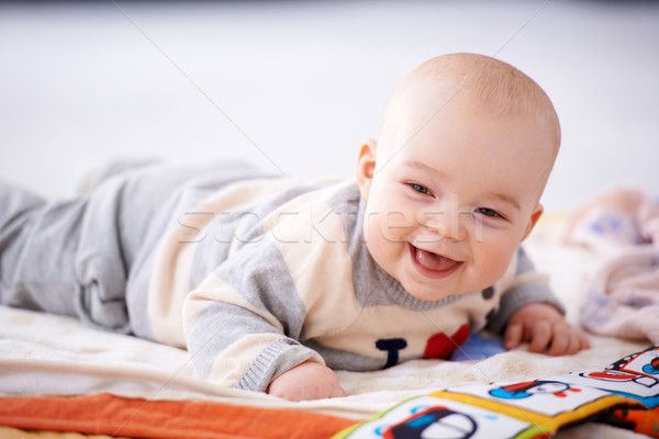 Stock photo: Happy gurgling baby lying on his bed