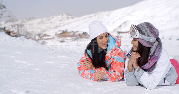 Giggling twins laying down at ski slope Stock photo © dash