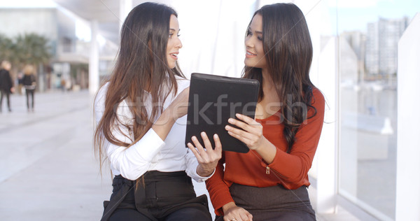 Two women discussing information on a tablet Stock photo © dash