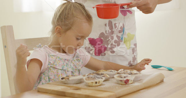 Child interested in sugar falling on baked muffins Stock photo © dash