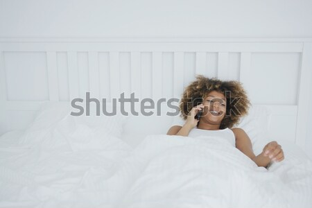 Content woman awakening in bed Stock photo © dash