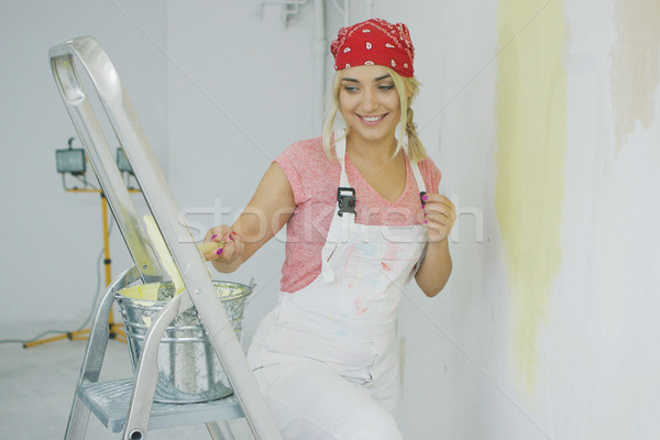 Happy female dipping brush in wall paint  Stock photo © dash
