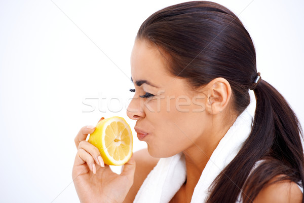 Woman holding lemon while making a face Stock photo © dash