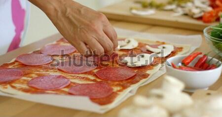 Woman making a delicious pepperoni pizza Stock photo © dash