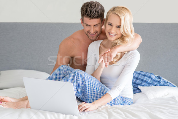 Young couple relaxing in bed using a laptop Stock photo © dash