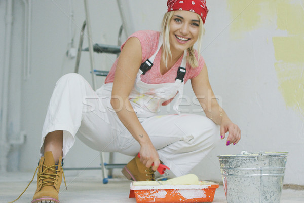 Smiling female dipping paint roller in tray Stock photo © dash