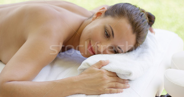 Disrobed woman lays belly down on table Stock photo © dash