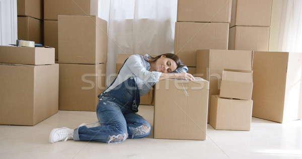 Tired young woman taking a break from packing Stock photo © dash