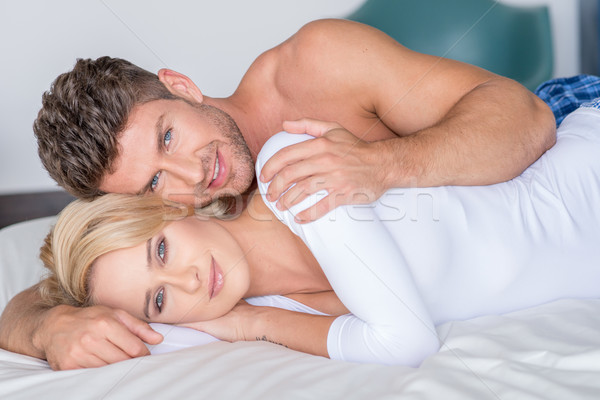 Sweet Young Lovers Lying on Bed Looking at Cam Stock photo © dash
