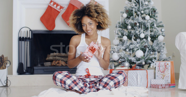 Stock photo: Pretty smiling woman displaying a Christmas gift