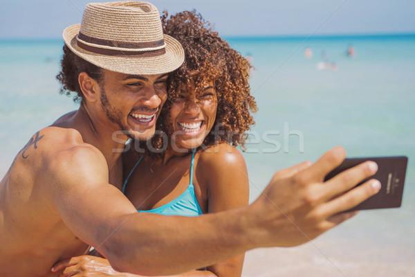 Cheerful happy couple selfies on beach Stock photo © dash