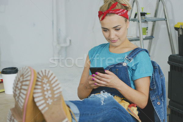 Smiling woman using smartphone sitting at workbench  Stock photo © dash