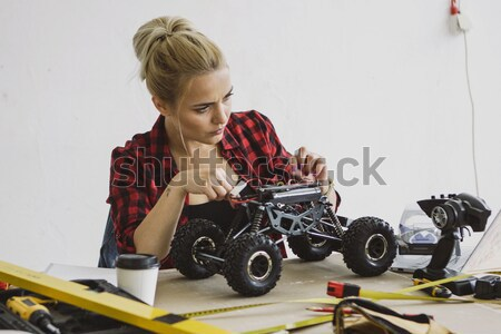 Woman playing with radio-controlled car in workshop Stock photo © dash