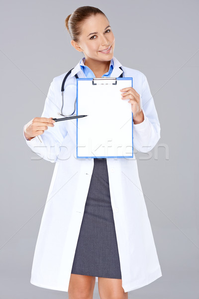 Female doctor displaying a blank clipboard Stock photo © dash