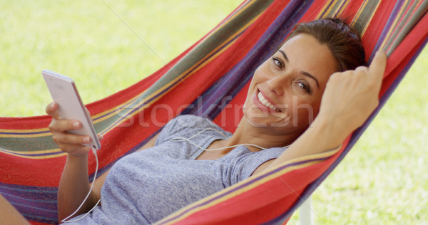 Happy young woman listening to music in a hammock Stock photo © dash